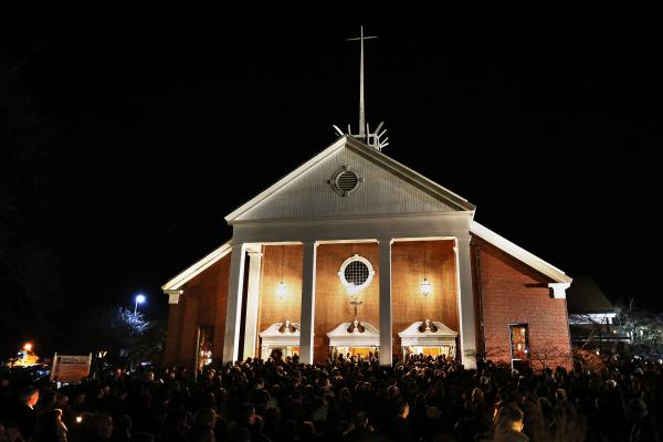 People gather outside a vigil at the Saint Rose of Lima church in Newtown. A gunman opened fire on schoolchildren and staff in Newtown at Sandy Hook Elementary School today.