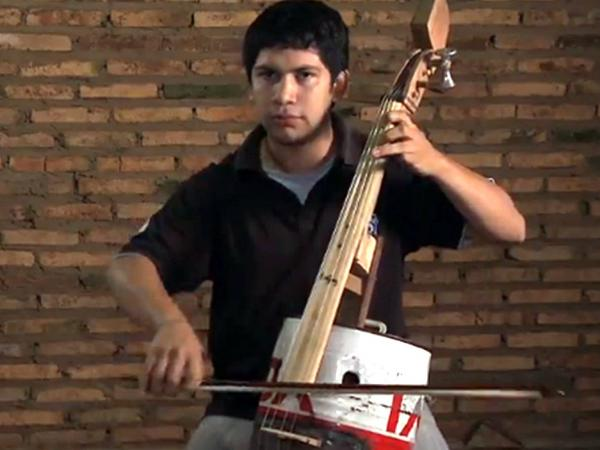 Cellist Juan Manuel Chavez, whose instrument is made from an oil can and discarded bits of wood.