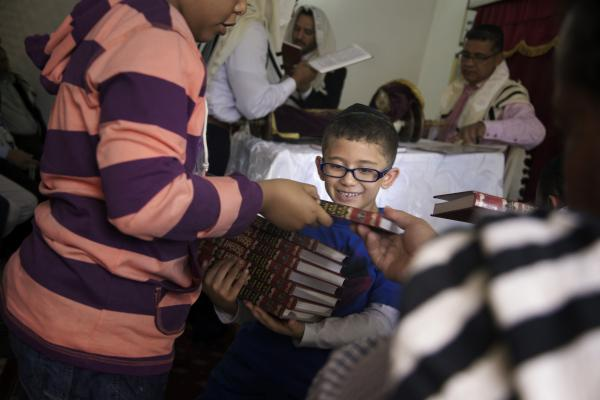 A boy collects books after prayers.