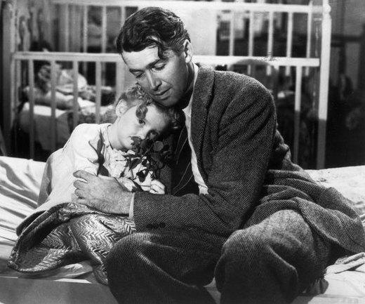 James Stewart, as George Bailey, hugs Karolyn Grimes, who plays his daughter Zuzu, in Frank Capra's <em>It's a Wonderful Life</em>.