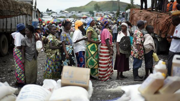 Congolese women wait for food to be distributed at the Mugunga III camp for displaced people outside the eastern town of Goma on Dec. 2.