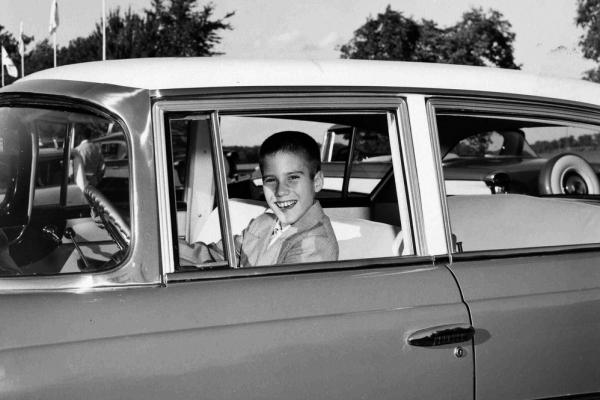 A young Mitt sits behind the wheel of his father's Rambler.