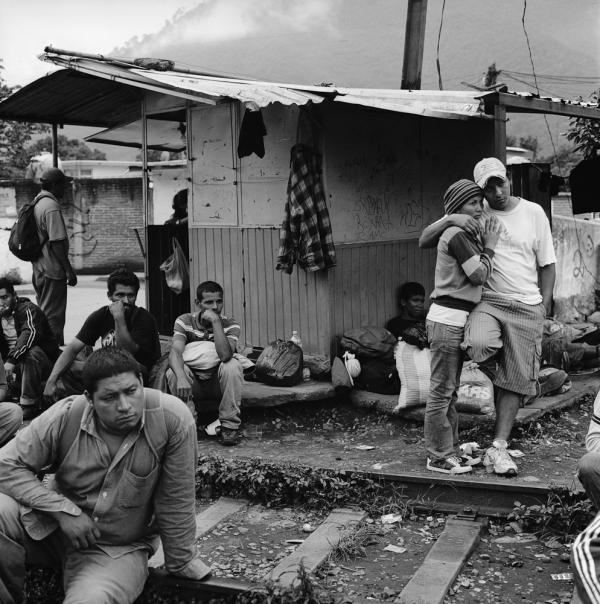 Migrants wait for a train by the tracks in the city of Orizaba in the Mexican state of Veracruz. There is no migrant shelter in Orizaba, and migrants wait out in the open, often for days, to catch moving freight trains. July 2010.