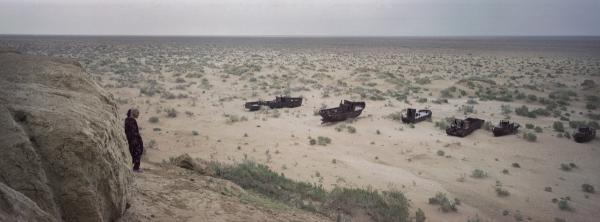 A local woman sees abandoned ships in what used to be the Aral Sea, May 2012. The Aral Sea has been shrinking since the 1960s because of irrigation projects.