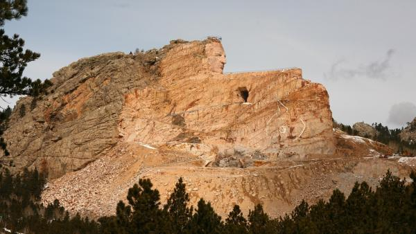 "The Crazy Horse monument in March 2012. When finished, it is expected to be 641 feet long and 563 feet high. It is <a href=""http://crazyhorsememorial.org/crazy-horse-memorial-facts/"">the largest mountain</a> carving in progress."