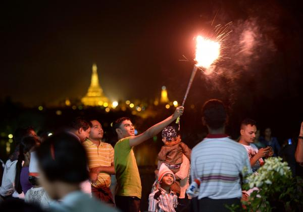 People wait before the countdown to the New Year near the Shwedagon Pagoda in Yangon, Myanmar. Some 50,000 people were expected to gather for the city's first ever public countdown to the New Year and fireworks.