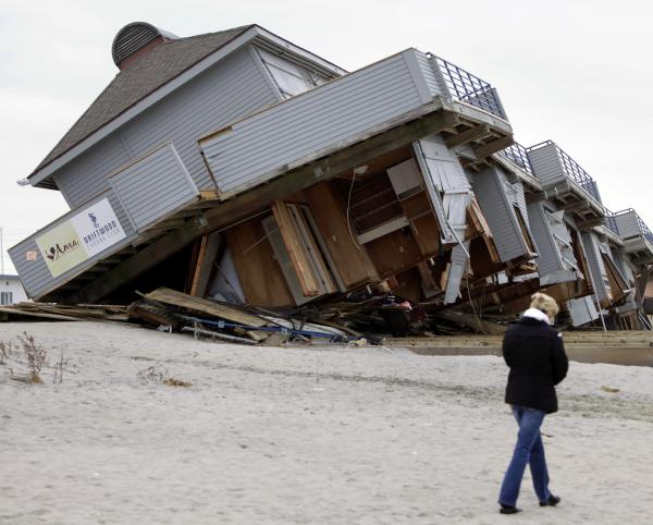 A woman walks past a cabana complex pulled off its foundations by Superstorm Sandy in Sea Bright, N.J., in November.