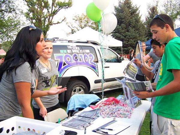 Altagracia Herrera, 25, shares information about a young professionals group with other young people at the recent Rock the Vote event in Richland. Photo by Anna King