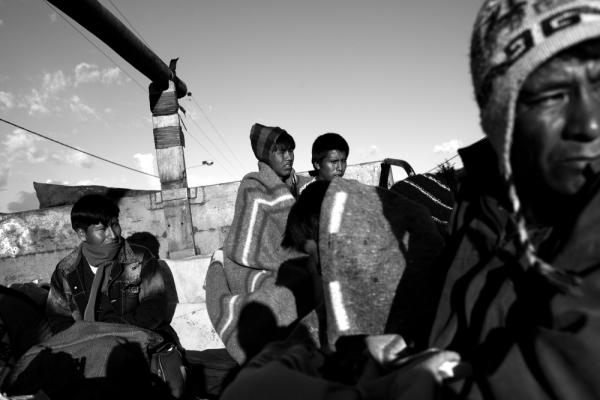 Teenage brothers Fredy and Saman Mamani (center) huddle together to stay warm as they travel atop a gas truck from the Andean crossroads town of Urcos, down into the Amazon Basin where they work in an informal gold mining camp.