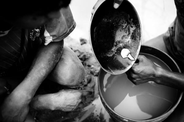 After 12 hours of dredging and another hour separating the gold particles from the sediment, a young miner pours the gold amalgam — a mix of liquid mercury and gold particles — into a container, which will then be taken to a gold shop where the mercury is burned off, leaving raw gold.