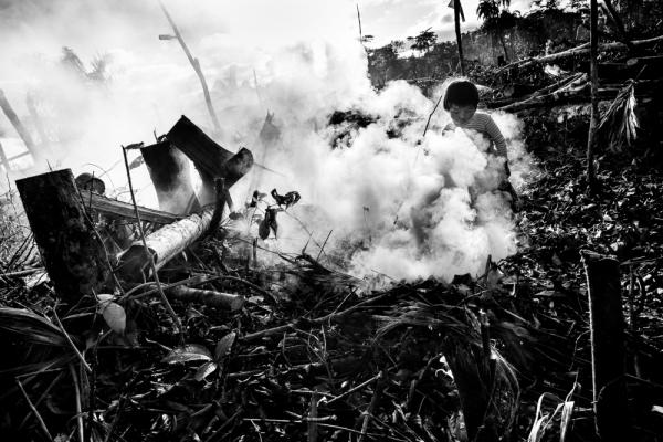 As his parents clear trees in the jungle so they can build a new home, a child plays in the smoke of burning brush and trees. In addition to the deforestation taking place from the actual gold mining process, migrant mining families who want to settle in the region and live outside of camps are also clearing swaths of the jungle as they establish new communities.
