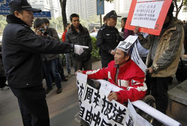 A policeman points to a supporter of <em>Southern Weekly</em> before taking him away during a protest near the newspaper's headquarters Thursday.