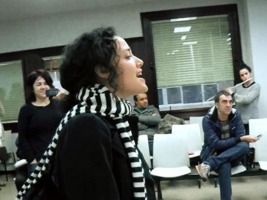 "A woman sings ""Here Comes the Sun"" by the Beatles in an unemployment office in Spain as part of a flash mob organized to cheer up those waiting in the office to find work."