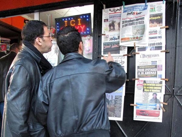 Algerian men look at national newspapers headlining the terrorist attack and kidnapping in Amenas at a news stand in Algiers on Thursday.
