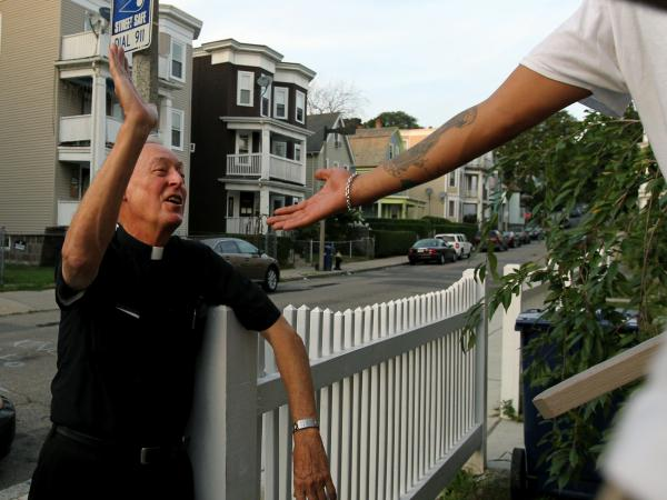 "Father Richard ""Doc"" Conway, of St. Peter Church, high-fives a man while walking the neighborhood on a Friday night."
