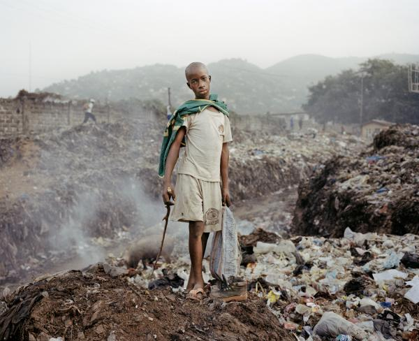 Ibrahim, 12, burns for copper in the Ferry Junction dumpsite that receives a large portion of Freetown's waste.