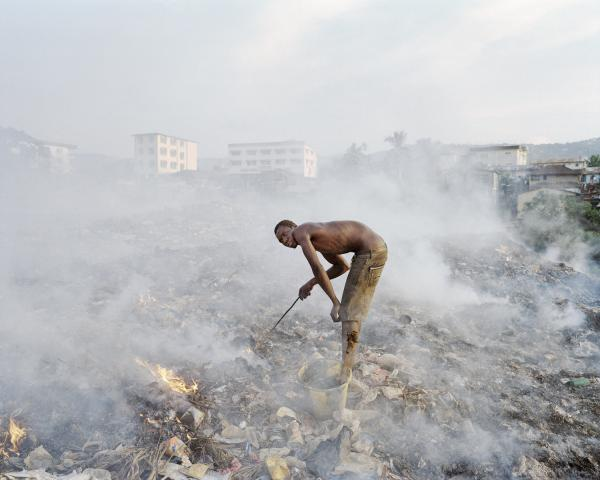 Young men stand in a wasteland burning garbage for copper. In the rainy season, which stretches from May to December, shanty houses at the base are flooded with water and refuse. In the dry season, stagnant pools of water build up and are used as alternative sources of water to wash.
