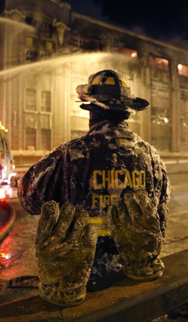 A frozen pair of gloves belonging to a Chicago firefighter stand on a railing behind him, during a five-alarm blaze in a warehouse on the city's South Side.
