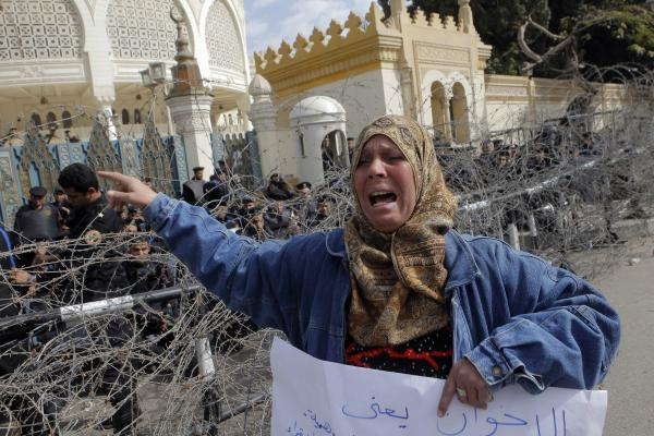 An Egyptian protester shouts anti-President Morsi slogans as anti-riot forces block the entrance to the presidential palace in Cairo, Egypt, Friday, Jan.25, 2013.