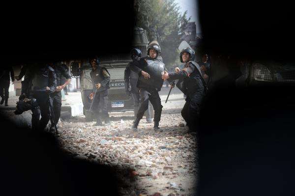 Egyptian security forces are seen through a hold in the wall, as they throw stones at protesters in Sheikh Rayhan street, that leads to the Interior Ministry headquarters, near Tahrir Square, on January 25, 2013.
