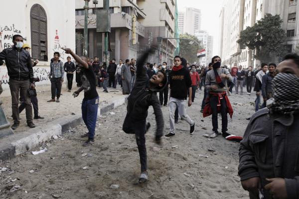 An Egyptian protester throws a rock toward riot police during a demonstration in Tahrir Square on January 25, in Cairo, Egypt.