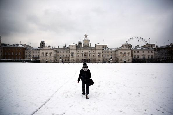 A man walks across a snowy Horse Guards Parade in London, England.