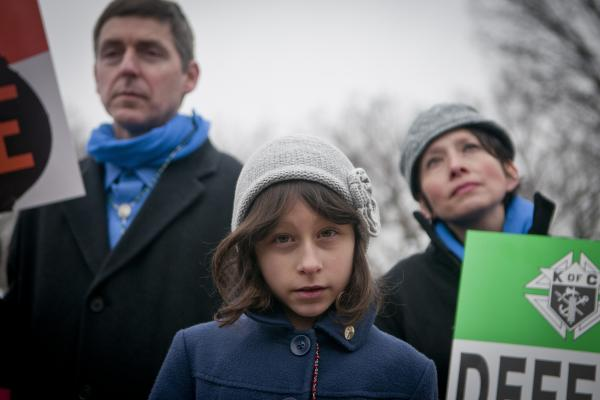 "Lucia Dragas, 8, from Boston, Mass., held a poster saying ""Defend Life"" along with her parents during the rally."