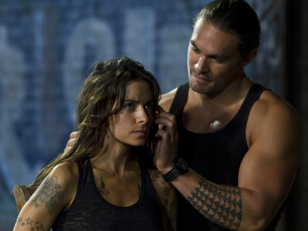 Sarah Shahi's tattoo artist — who has ties to both Kang and Stallone's characters — falls into the clutches of a mob enforcer (Jason Momoa)<em>.</em>