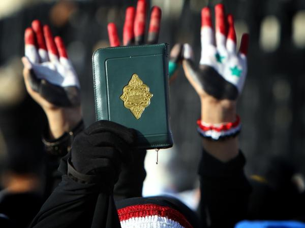 <p>A Yemeni woman in the capital Sana'a holds up a copy of the Quran while others raise their palms painted with the colors of the Yemeni (left), Libyan (center) and Syrian flags during a demonstration on Monday against President Ali Abdullah Saleh.</p>