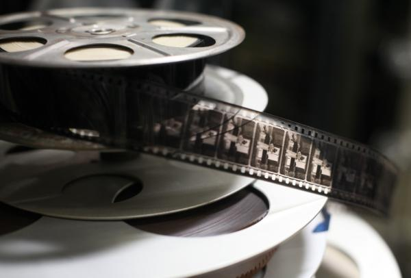This '40s-era film reel contains early unknown black-and-white footage, likely from the silent movie era. The reels beneath it are later split reels, likely the ones used in <i>Good Night and Good Luck</i>.