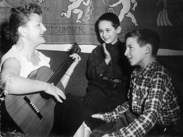 Anne Meeropol plays a song on guitar for her sons, Robert and Michael.