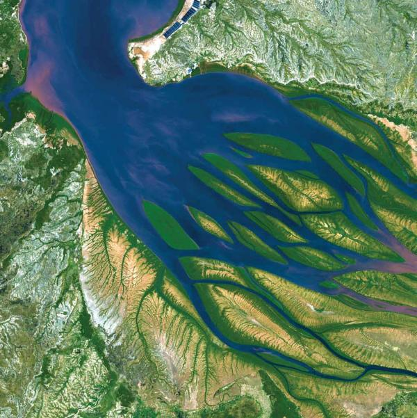 <p><strong>Bombetoka Bay, Madagascar, 2000</strong></p><p>Islands and sandbars have formed where the Betsiboka River flows into the Mozambique Channel. The past few decades have seen a dramatic increase in the amount of sediment moved by the river and deposited in the estuary. Dense vegetation is deep green, and water is sapphire, tinged with pink where sediment is particularly thick.</p>