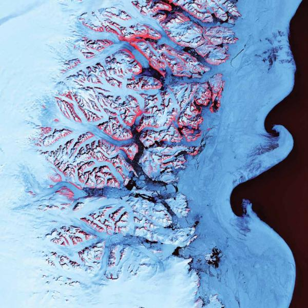 <p><strong>Ice Waves, Greenland, 2001</strong></p><p>The undulating swirls shown here along the eastern coast of Greenland are slurries of sea ice, newly calved icebergs, and older weathered bergs. During the summer melting season, the southward-flowing East Greenland Current twirls these mixtures into stunning shapes. The exposed rock of mountain peaks are tinted red.</p>