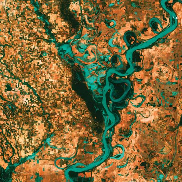 <p><strong>Meandering Mississippi, U.S., 2003</strong></p><p>Graceful swirls and whorls of the Mississippi River encircle fields and pastures on the border between Arkansas and Mississippi. The Mississippi is the largest river system in North America and forms the second largest watershed in the world.</p>