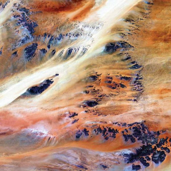<p><strong>Terkezi Oasis, Chad, 2000</strong></p><p>A series of rocky outcroppings emerge from the sand in the Sahara Desert near the Terkezi Oasis. Stretching across the immense desert are vast plains of sand and gravel; seas of sand dunes; and barren, rocky mountains. Only 10,000 years ago, grasses covered the region, and mammals such as lions and elephants roamed the land.</p>