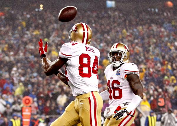 Randy Moss of the 49ers glides down the field, under an arcing football, on his way to a touchdown against the Patriots on December 16, 2012.