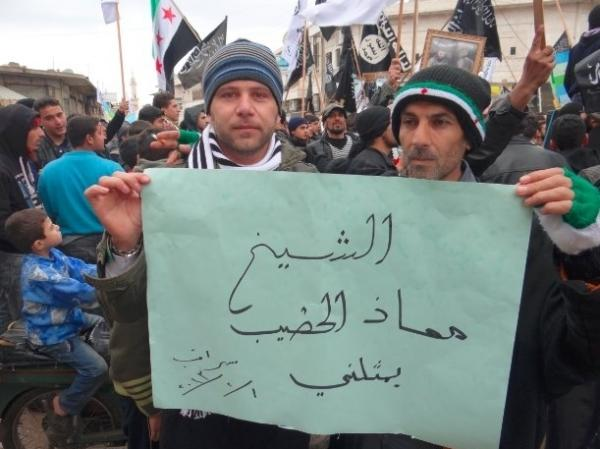 "Activists in the town of Saraqib, Syria, hold a poster that reads, ""Sheikh Moaz al Khatib represents me."""