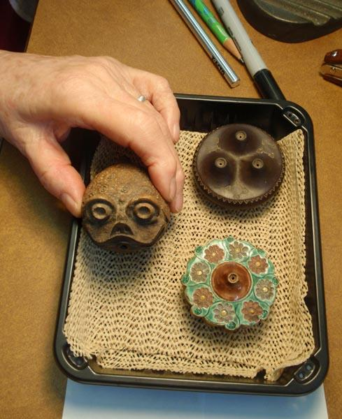 Ceramic opium pipe bowls; the center one has a toad design. Photo by Tom Banse
