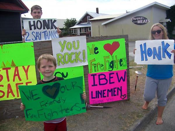 Chase Stanley, 15, of Cle Elum, and his siblings wave to passing motorists with signs supporting the firefighters at the Taylor Bridge Fire in central Washington. Photo by Anna King