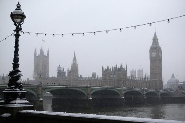 Snow falls on the Houses of Parliament in London in January.