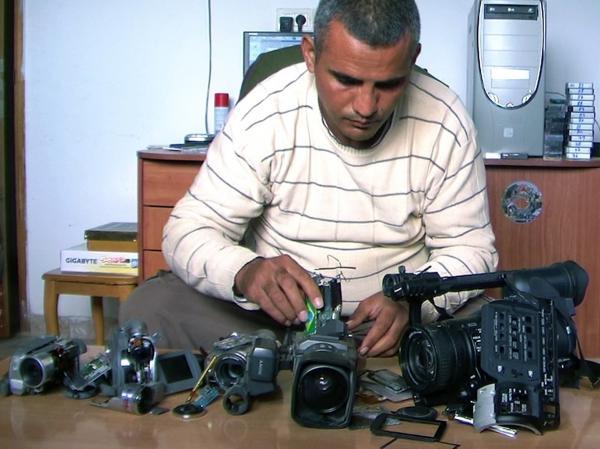 Co-director Emad Burnat examines his five broken cameras.