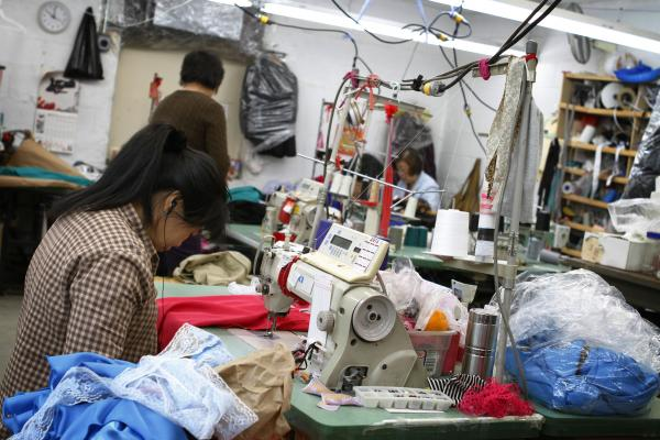 A seamstress works on a garment in the factory Yee contracts to produce her line. While the final product of high-end fashion is crisp and clean, the beginning stages can easily be described as creative chaos.