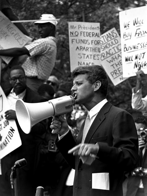 "Attorney General Robert F. ""Bobby"" Kennedy uses a bullhorn to address a crowd of demonstrators, June 14, 1963, at the Justice Department. Four months earlier he had walked 50 miles in one day to prove to his brother John that he could do it. His march helped make extreme walking and hiking popular activities."