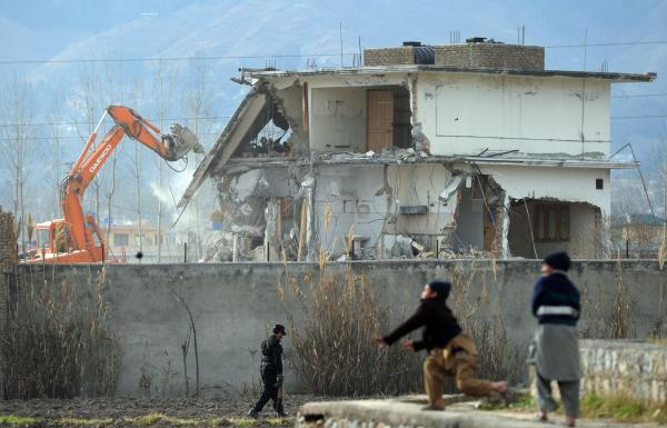 Young Pakistani boys play near demolition works while Osama bin Laden's compound in Pakistan is demolished.