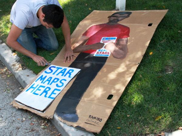 Gomez works on a piece that he later removed after a man selling maps to celebrities' homes threatened to take it down.