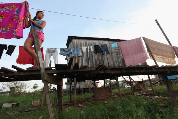 A resident stands in the low-lying Invasao dos Padres neighborhood, which stands to be flooded by the Belo Monte dam. Houses are constructed on stilts to protect against seasonal flooding. The government says residents forced to relocate because of the dam will be compensated, and that most will benefit from relocation.