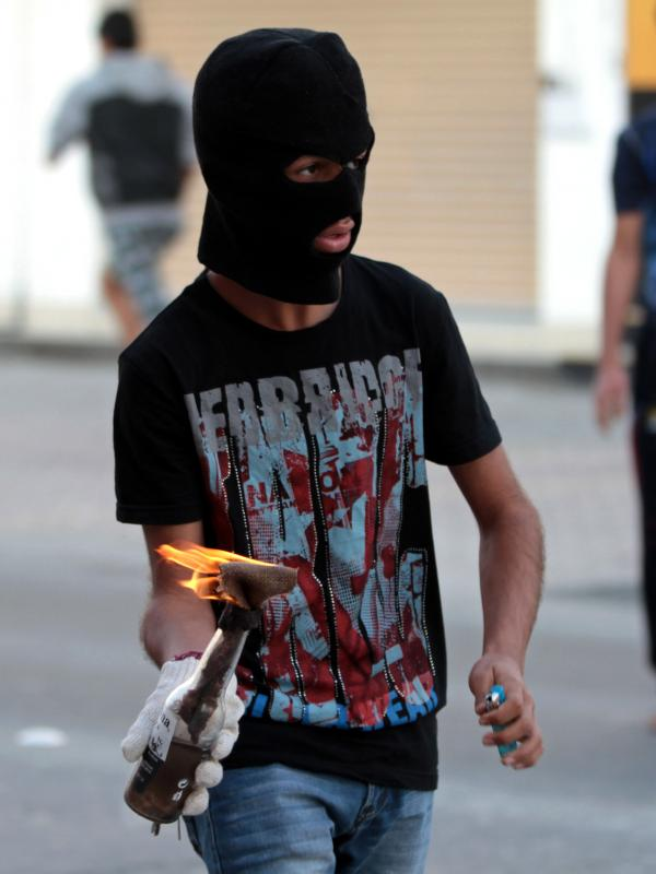 A Bahraini anti-government protester prepares to throw a Molotov cocktail at riot police during clashes in Malkiya village, Bahrain, on Jan. 7.