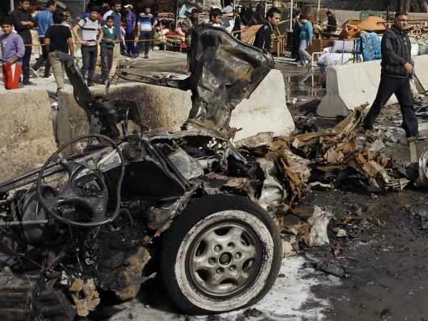 Iraqis inspect the scene of a car bomb attack in the Ameen neighborhood in eastern Baghdad on Sunday.