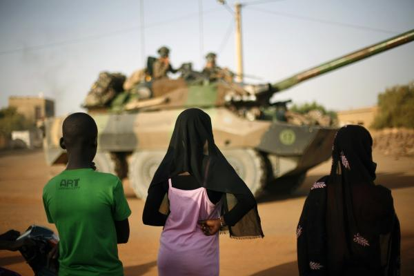 Malian teenagers watch French soldiers pass through Gao, in northern Mali, Tuesday, Feb. 19, 2013.