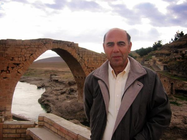Esho Joseph stands in front of the Nemo Delale bridge in Zakho, Iraq. Joseph, a former translator, grew up speaking Aramaic.